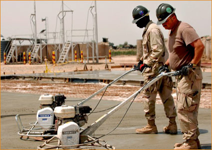 US Seabees using steel paving forms to finish concrete foundation work for a vehicle maintenance building